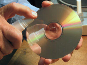 Hold cd by edges, spray shiny side lightliy